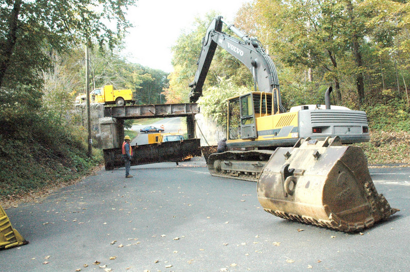 Workmen used a cutting torch and some heavy equipment on the morning of Friday, Octo-ber 2, to disassemble a bridge section which was heavily damaged on Thursday, October 1, when the cargo protruding upward from a heavy dump truck collided with the Housatonic Railroad's railroad bridge above Botsford Hill Road. The section of Botsford Hill Road near the bridge was reopened to traffic midday Friday, October 2, after having been closed for about 10 hours. – Bee Photo, Gorosko