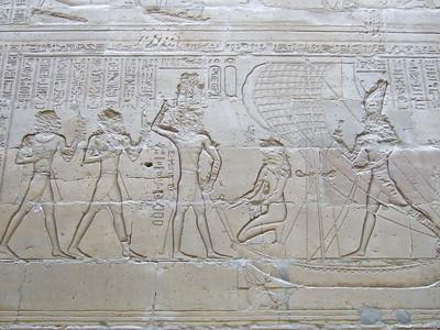 Wall carvings inside Edfu Temple. Looks like a Pharaoh on a sailing boat.
