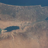 Earth's lowest elevation on land, one of the saltiest bodies of water, with minuscule quantities of life. ISS over the Middle East. (ANSWER: The Dead Sea)