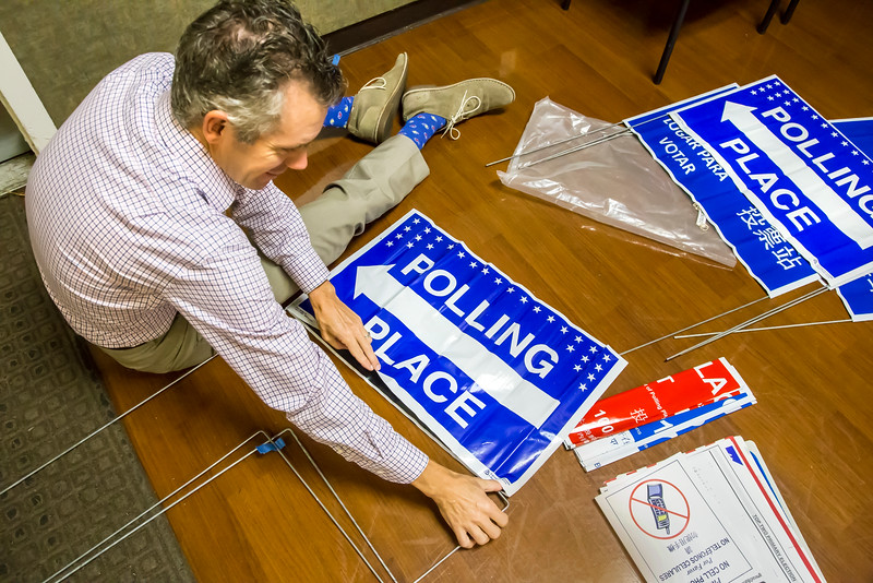 Poll worker Eric Johnson assembles outdoor signs for the polling place at Sierra 2 Center. Johnson and other poll workers arrive at 6 a.m. for set-up to be ready when doors open to voters at 7 a.m.