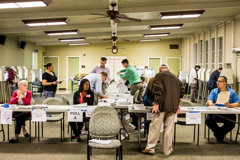 The last voter of the day, Richard Aston, checks into Poll B at Sierra 2 Center as election inspectors Geoffrey Neill and Tony Sertich (center) prepare for the final count of votes, provisional ballots and mail-in ballots delivered to the poll.