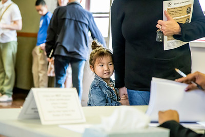 """Four-year-old Elliott Webb hides behind her mother, Toni Webb, who checks in to obtain her ballot. Photos and story on """"A Day in the Life of a Neighborhood Precinct"""" for Comstock's online.  http://www.comstocksmag.com/photo-gallery/day-life-neighborhood-precinct"""
