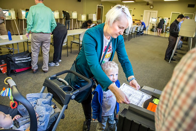 Samson Kelahan helps his mother, Kristen Schumacher, scan her completed ballot, as baby Lincoln watches from his stroller.