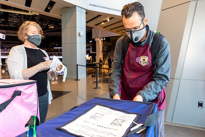 """Voter Tim McEvilly deposits his paper ballot at the Golden 1 Center. Elections worker Ann Nakamura (left) prepares his """"I Voted"""" sticker."""
