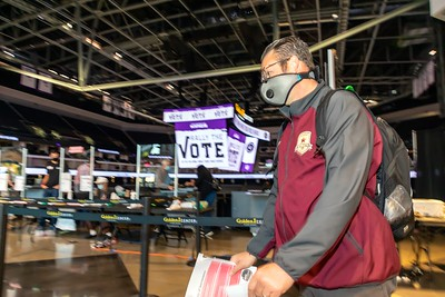 Voter Tim McEvilly of Sacramento heads to the second check point to pick up his paper ballot.