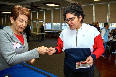 """Poll worker Judy Kreizenbeck hands an """"I voted"""" sticker to Valentina Polendo-Rodriguez at the Sierra 2 Center Vote Center on March 3, 2020."""