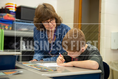 Cecilia kirsch looks over Noah Connors, 6, as he completes his assignment during their 1st grade class at Harold O. Brumsted Elementary School