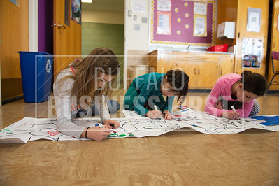 Fourth graders Rebeckah Dracup, 10, Shannon Fisher, 9, and Teagan Krywalski, 9, program Ozobots in the Library at Harold O. Brumsted Elementary School