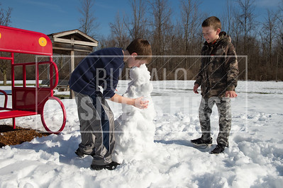 5th graders Nicholas Russell and Callan Moyer, both 10, make a snowman during recess at Ledgeview Elementary School.