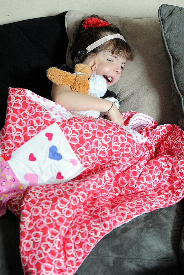 Chloe Cooper, 6, snuggles on the couch with a blanket that Santa Claus gave her during a special visit to her Loveland home Sunday, Dec. 20, 2015. (Photo by Jenny Sparks/Loveland Reporter-Herald)