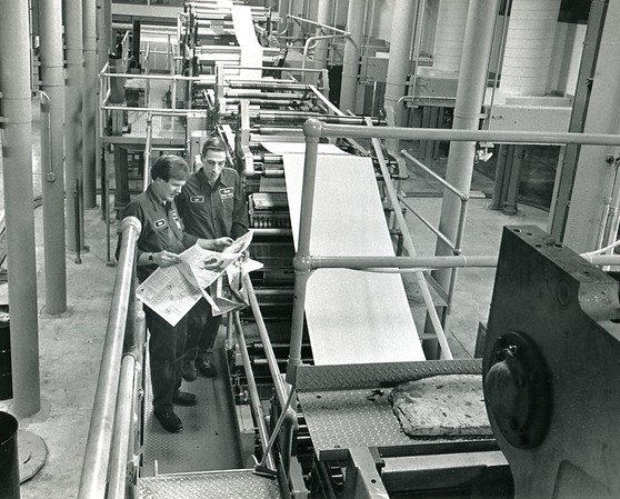 Pressmen Richard Arienti and Nando Delmolino leaf through papers at the Clocktower press in one of the first press runs in 1990.