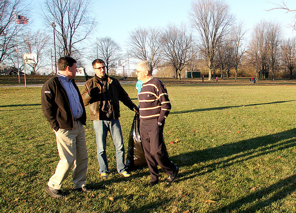 Volunteer Dustin O'Brien (center) takes a break during a cleanup Monday afternoon at Abner Longley Park in Lebanon to talk to Indiana Congressman Todd Rokita, left, and Lebanon Mayor Huck Lewis.