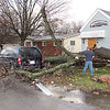 Reporter photo by Rod Rose<br /> An unidentified man uses a chain saw to remove part of a tree that fell onto this van on South Meridian Street after a tornado caused extensive damage in Lebanon Sunday.