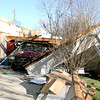 Reporter photo by Rod Rose<br /> A roof section was torn off, and the garage collapsed on a pickup, at a South Meridian Street home by an EF-2 tornado Sunday. Friends of the tenant, who all declined to be identified, were helping the man move his belongings Monday.