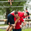 Midshipman captain Harvey 1st class Regimental Commander being carried during a man down drill portion of the obstacle course during obstacle course training at SUNY Maritime College on July 14th, 2014. At the end of candidate training, indoctrination officer teams race to determine if the candidate class they are racing for will be allowed temporary special privileges.