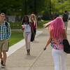 Student with pink hair crossing campus at SUNY Buffalo State.