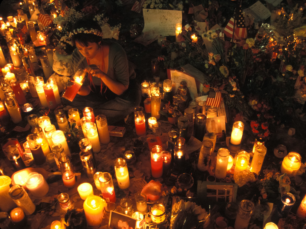 A woman lights a candle at a memorial in Union Square Park