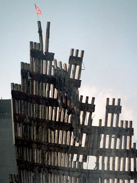 Workers place an American flag high atop the remains of the World Trade Center
