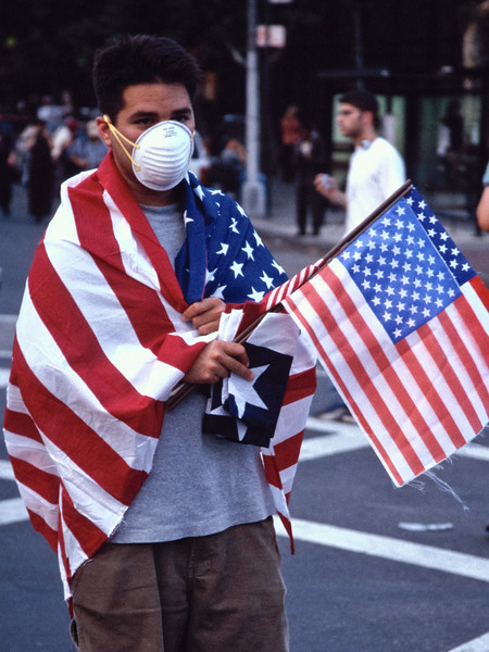 New Yorker draped in the American flag in the dusty streets near Ground Zero