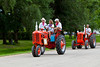 A procession of restored vintage farm tractors at the Tractor Trek event in Reinland, Manitoba, Canada.