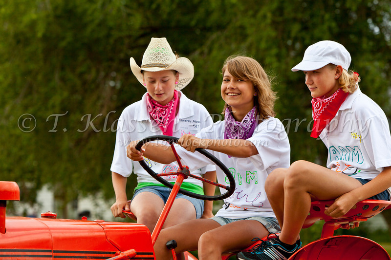 Three young girls driving a restored vintage farm tractor at the Tractor Trek event in Reinland, Manitoba, Canada.