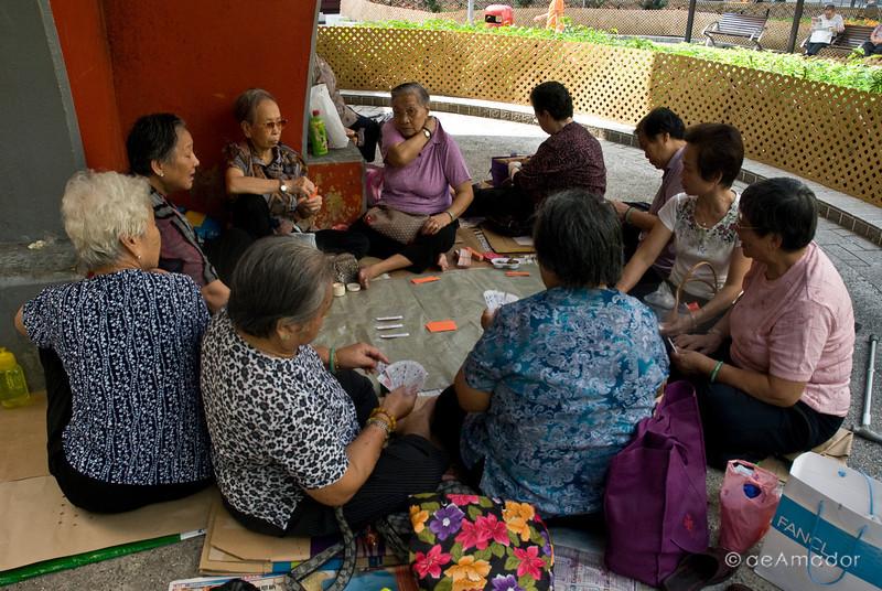 aeamador©-HK08_DSC0021 Saukiwan market. Saukiwan, Hong Kong island.  <br /> Senior ladies playing cards in a nearby square.