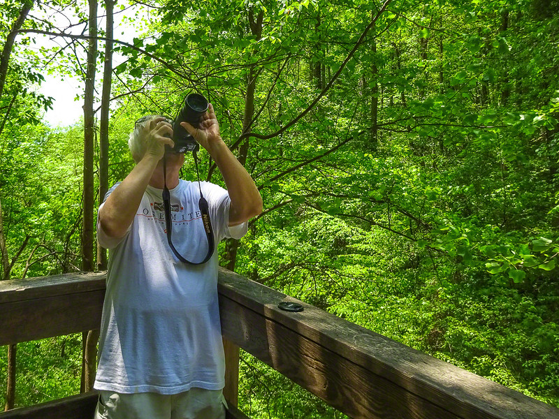 He's taking in the view and surroundings or taking pictures.
