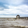 Lake Pontchartrain has white caps in high wind.  The brackish water is churned by the wind and waves resulting in a muddy appearance close to shore.