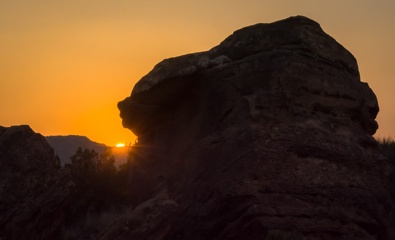 The last rays of the day peaking around a huge boulder