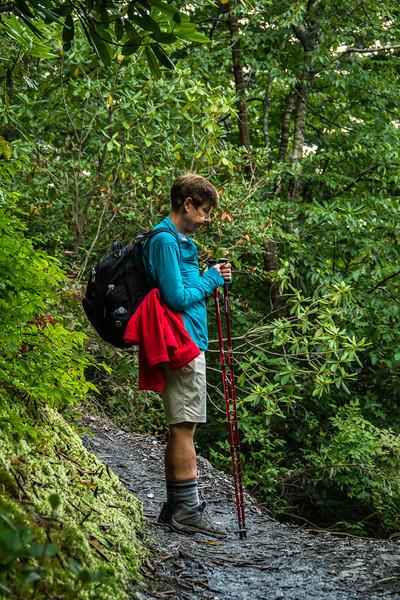 Deb pondering a dropoff hidden by dense foliage