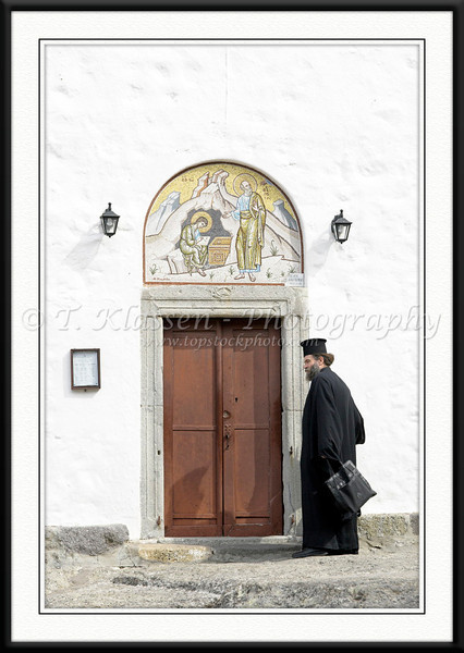 A Greek Orthodox priest at the entrance to the Monastery of the Apocalypse on the island of Patmos, Greece.
