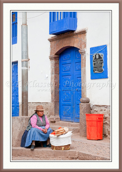 A Peruvian lady in traditional dress selling bread in Pisac, Urubamba Valley, Peru, South America.