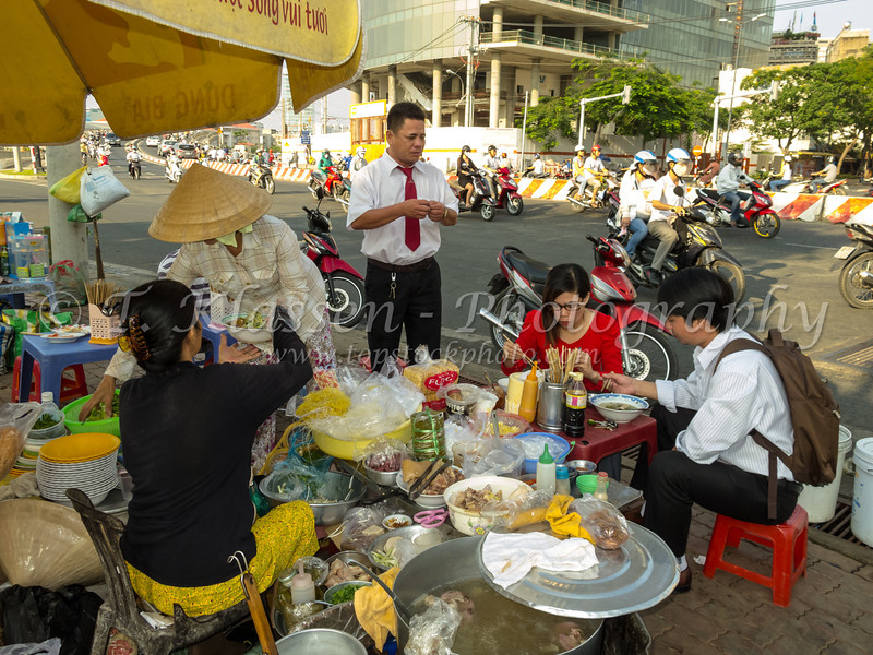 Local people eating breakfast on the street in Saigon, Vietnam, Asia.