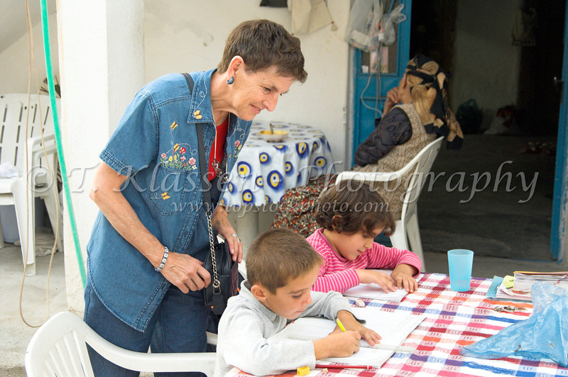 Esther Anne inspecting the schoolwork of two Turkish children in the village of Karahayit near Hierapolis, Turkey, Eurasia.