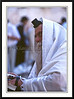 An orthodox Jewish man wearing a prayer shawl reads from the prayer book at the Western Wall in Jerusalem, Israel.