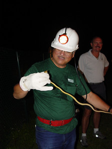 Nilton Matayoshi (Hawaii Department of Agriculture) captures a brown tree snake (Boiga irregularis) in a trap (Guam, May 2003) OK to use this image in publications courtesy of CGAPS