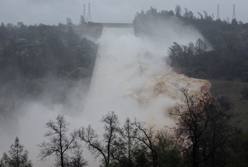 . The hole from the damaged Oroville Dam controlled Spillway continues to grow larger as approx. 30,000 cfs of water is released Thursday Feb. 8, 2017.  Erosion along the damaged spillway continues but releases of water remain necessary as rain continues Thursday.   (Bill Husa -- Enterprise-Record)