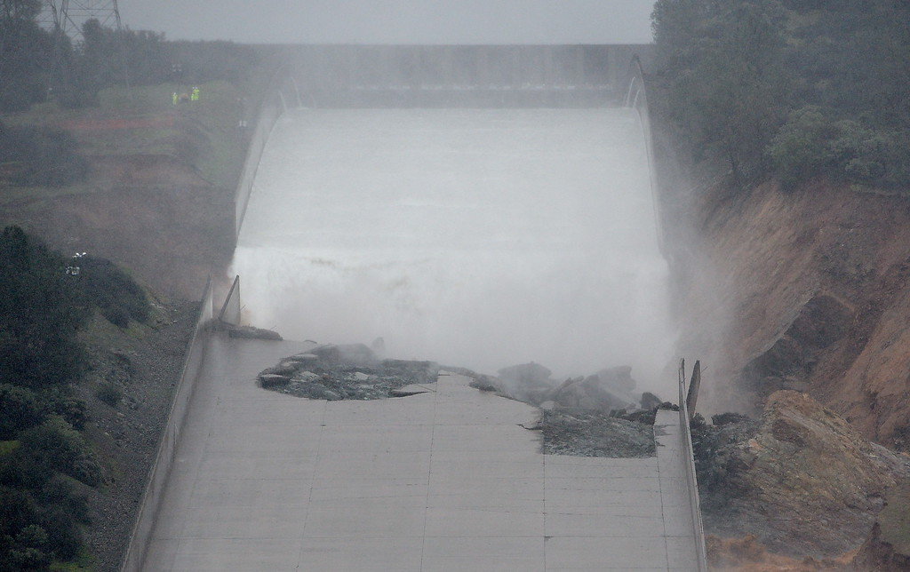 . The hole from the damaged Oroville Dam controlled Spillway fills with water during the start of the water release Thursday. The hole continues to grow larger as water is released Thursday Feb. 8, 2017.  Erosion along the left side continues to increase as the spillway falls apart. (Bill Husa -- Enterprise-Record)
