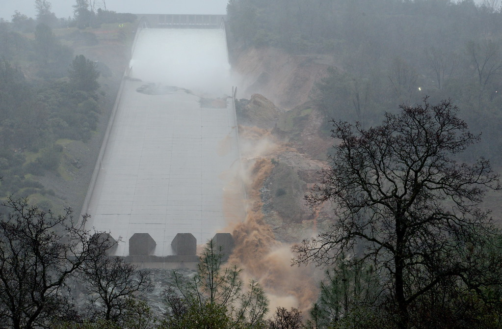 . Mud and debris begin to travel down the side and the remaining spillway as water is released Thursday. The hole from the damaged Oroville Dam controlled Spillway continues to grow larger as water is released Thursday Feb. 8, 2017.  Erosion along the left side continues to increase as the spillway falls apart. Water continues to be released in an effort to avoid using the emergency spillway on the far side (not visible) of the dam. (Bill Husa -- Enterprise-Record)