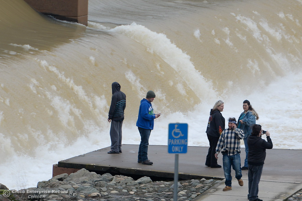 . People check out the water flow over the Fish Barrier Dam at the Feather River Fish Hatchery in Oroville, Calif. Tues. Feb. 7, 2017. The gates to the hatchery are closed. (Bill Husa -- Enterprise-Record)