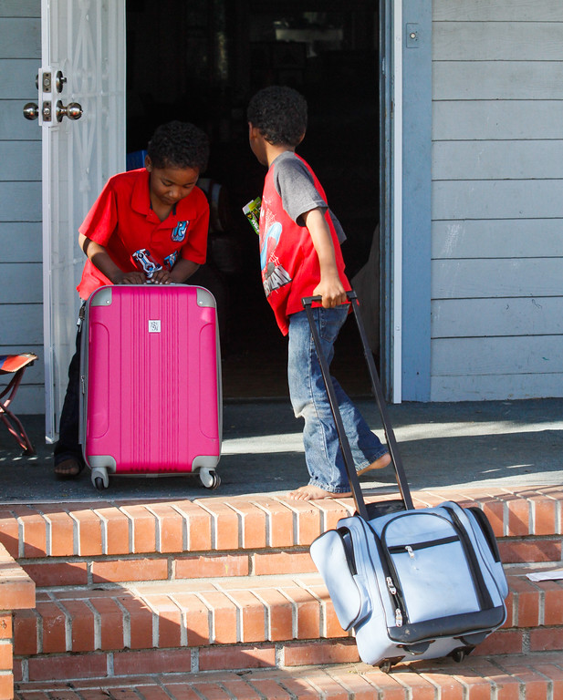. Twins Nathaniel and Steven Murphy, 5, help their mother Rebecca carry suitcases into their home after the mandatory evacuation was lifted and Oroville residents are allowed to go home for the first time since Sunday evening Tuesday February 14, 2017 in Oroville, California. (Emily Bertolino -- Enterprise-Record)