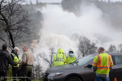 Media representatives, law enforcement and DWR employees are on scene along Oro Dam Blvd. East watching approx. 65,000 cfs of water flow down the damaged Lake Oroville Dam Spillway Friday Feb. 10, 2017. (Bill Husa -- Enterprise-Record)
