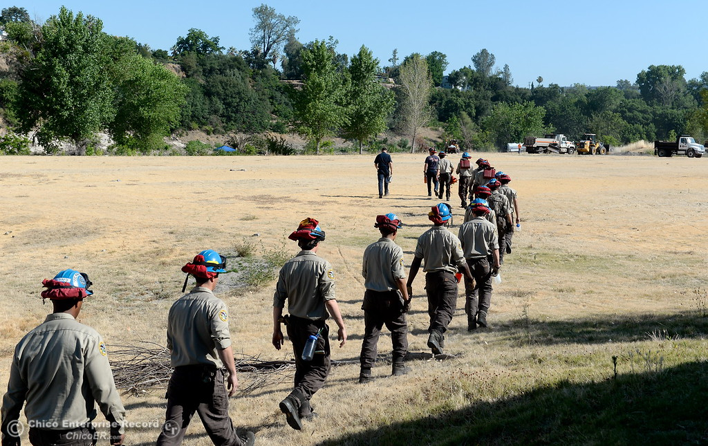 . California Conservation Corps members hike in to help as  groups from several agencies are working together to repair multiple issues in and around Riverbend Park in Oroville, Calif. Friday, June 23, 2017. (Bill Husa -- Enterprise-Record)
