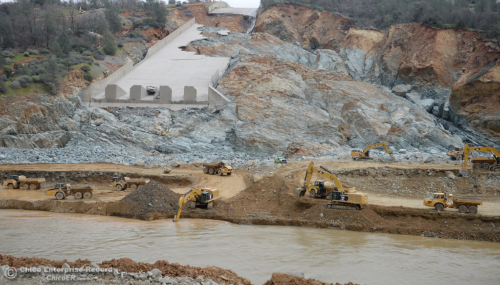 . Dump trucks and excavators are seen as work continues to remove debris from below the Oroville Dam spillway Monday March 6, 2017.  (Bill Husa -- Enterprise-Record)