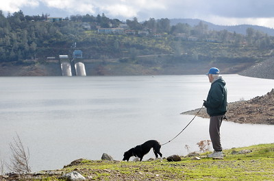 "Local resident Merrill Beck and his dog Lucy enjoy a walk near the Spillway Launch Facility at Lake Oroville in Oroville Calif. Wed. Jan 11, 2017. Beck said  ""It's amazing how fast it goes up and it goes down just as quickly. I think it has gone up 80 or 90' since this whole thing started."" (Bill Husa -- Enterprise-Record)"