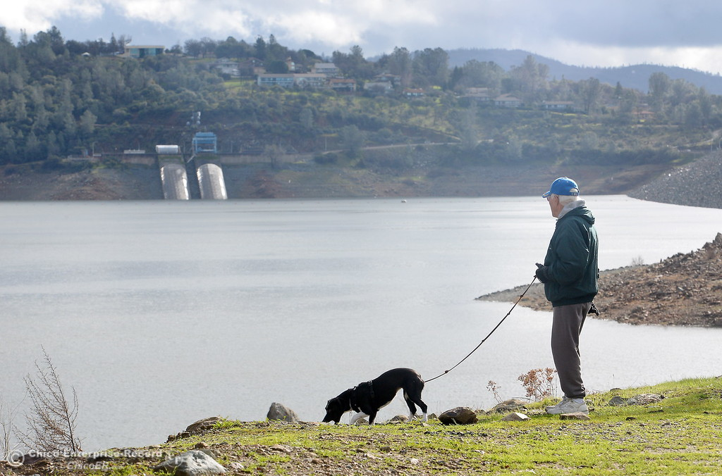 ". Local resident Merrill Beck and his dog Lucy enjoy a walk near the Spillway Launch Facility at Lake Oroville in Oroville Calif. Wed. Jan 11, 2017. Beck said  ""It\'s amazing how fast it goes up and it goes down just as quickly. I think it has gone up 80 or 90\' since this whole thing started.\"" (Bill Husa -- Enterprise-Record)"