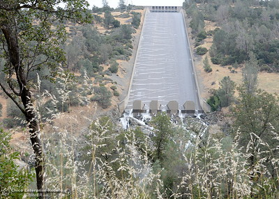 As the dry grass of summer grows along the road a bit more than a trickle continues to flow over the controlled spillway at the Oroville Dam in Oroville, Calif. Tuesday June 14, 2016. (Bill Husa -- Enterprise-Record)
