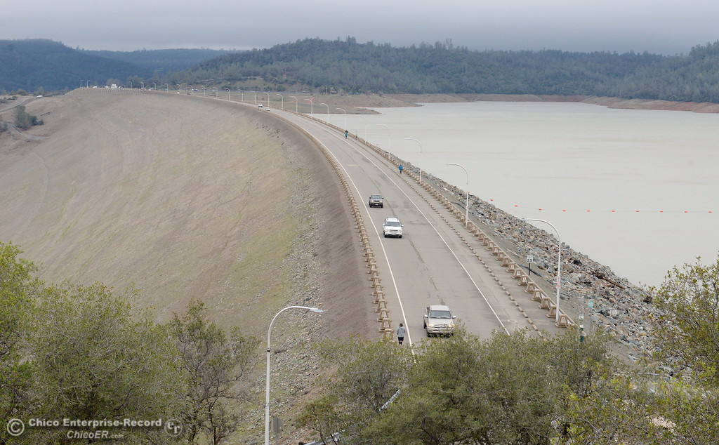 . People enjoy the view from the Lake Oroville Dam Tuesday. The Lake Oroville Dam Spillway has sustained erosion damage and some roads in the area are closed Tues. Feb. 7, 2017. (Bill Husa -- Enterprise-Record)