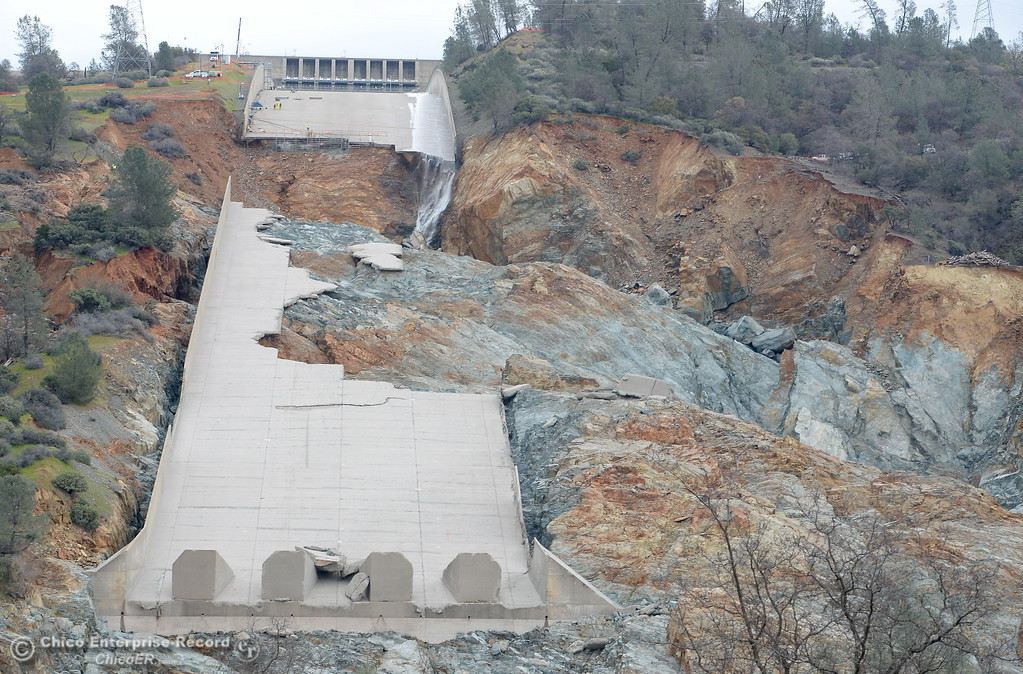. Although reports show a zero cfs outflow at the spillway, water, presumably leaking from the flow control system is seen flowing down one side as work continues to remove debris from below the Oroville Dam spillway Monday March 6, 2017.  (Bill Husa -- Enterprise-Record)