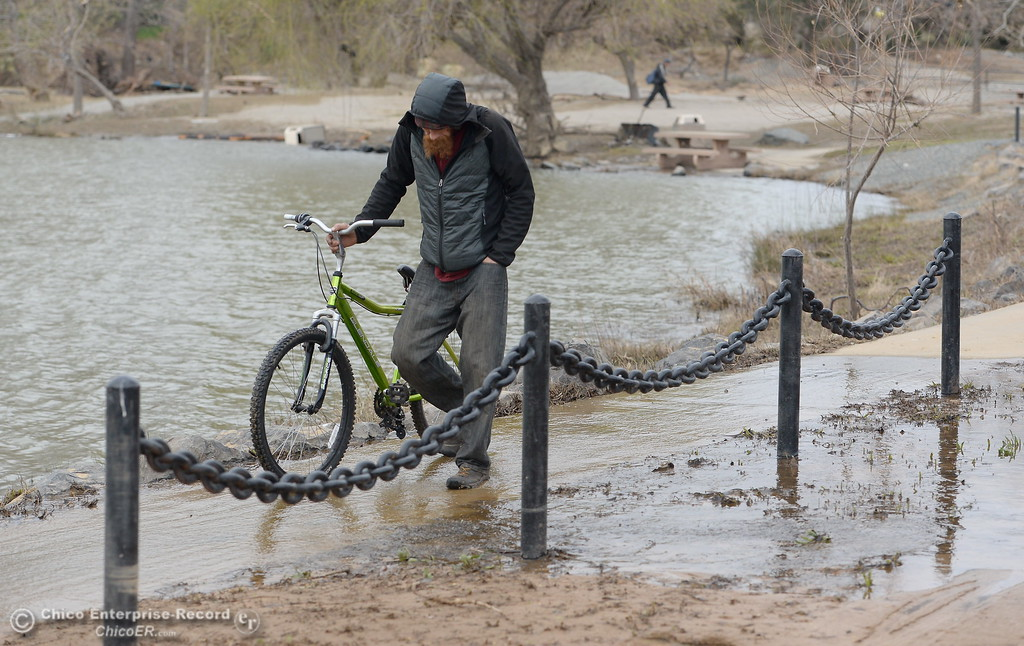 . Zach Anderson of Oroville walks his bike near the fishing pond at Riverbend Park seen during a tour of the damaged areas within the park Monday March 6, 2017. Anderson said he was just checking out the damage to the park however the park remains closed to the public for repairs. (Bill Husa -- Enterprise-Record)